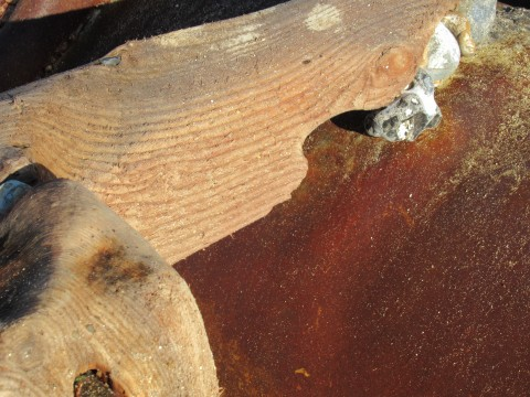 Red rust on pipe surface against word wood breakwater, with golden tones from sunshine