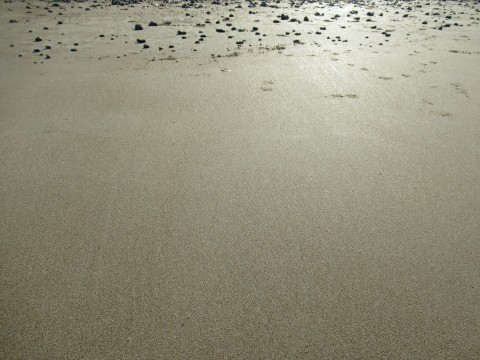 Smooth sand with small stones in the distance