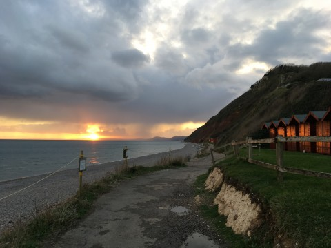 Branscombe beach, looking west towards the sunset, an orange glow reflecting on the beach huts